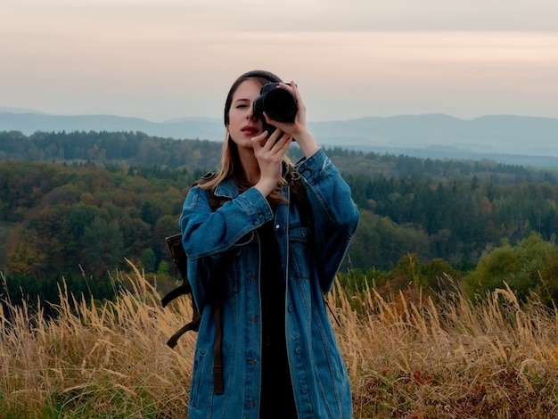 Style woman with photo camera and backpack at countryside with mountains