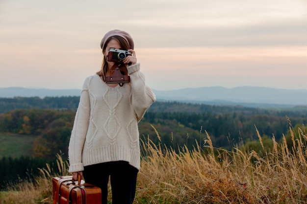 Style woman with suitcase and photo camera at countryside with mountains