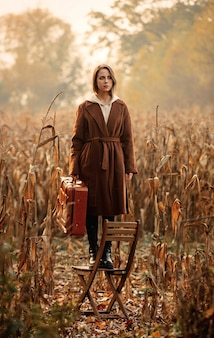 Style woman with suitcase stay on chair on corn field in autumn time season