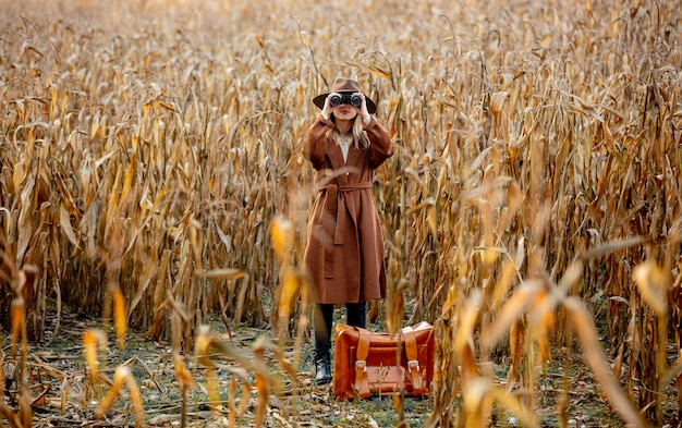 Style woman with travel suitcase and binoculars on corn field in autumn time season