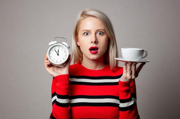 灰色の壁に警報時計と一杯のコーヒーが付いた赤いセーターのスタイルのブロンド