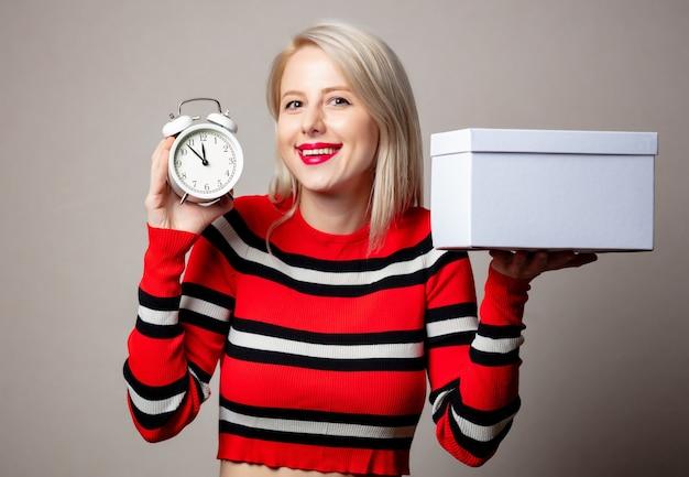 灰色の壁に目覚まし時計とギフトボックスが付いた赤いセーターのスタイルのブロンド