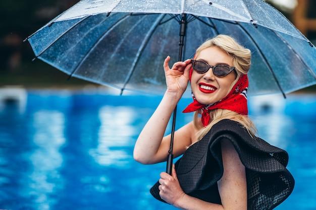 Стильная блондинка в темных очках держит зонтик в бассейне