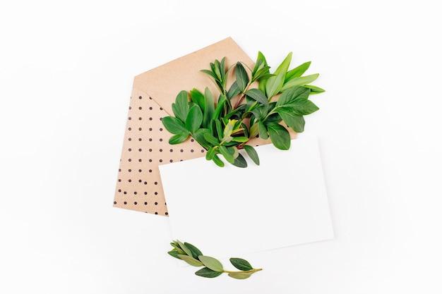 封筒、空白のカード、緑の葉と金の事務用品の構成を備えたスタイルのデスク。フラットレイ。