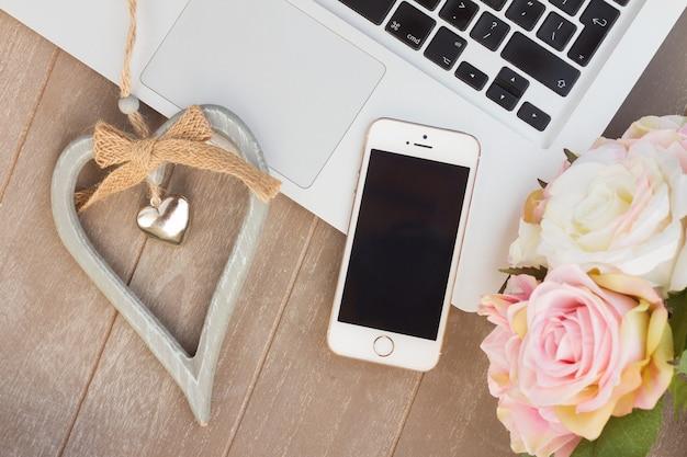 モダンな電話、ラップトップ、ハート、花を備えたスタイルのデスクトップ