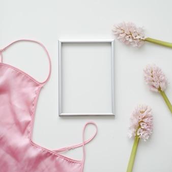空白のフォトフレーム、シルクのランジェリー、白い背景にピンクの花でスタイリングされたフェミニンなフラットレイ。上面図、コピースペース。