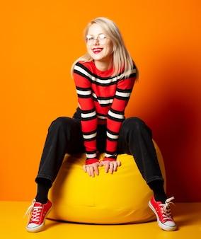 오렌지 벽에 노란색 콩의 자에 앉아 스타일 된 hipster 여자