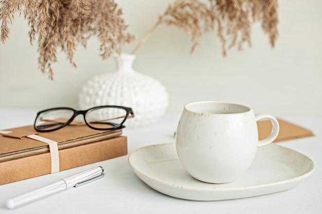 オーガニックカラーのステーショナリー、コーヒーカップを備えたスタイルのミニマルデスクトップ