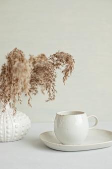 有機色のコーヒーカップと乾燥ハーブの花瓶を備えたスタイリングされたミニマルテーブル