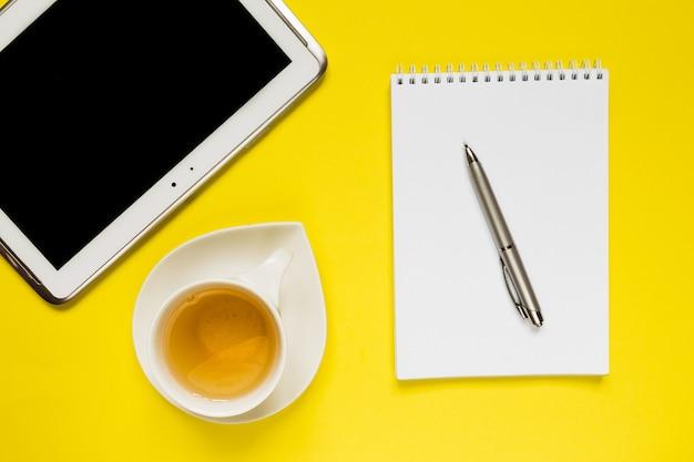 空白のノートブック、コンピューター、消耗品、ティーカップとスタイルの写真黄色オフィスデスクテーブル。