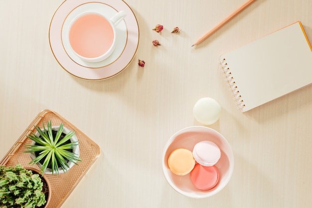 Стилизованный stock photography бежевый офисный стол стол с пустой ноутбук, миндальное печенье, принадлежности и чашка кофе