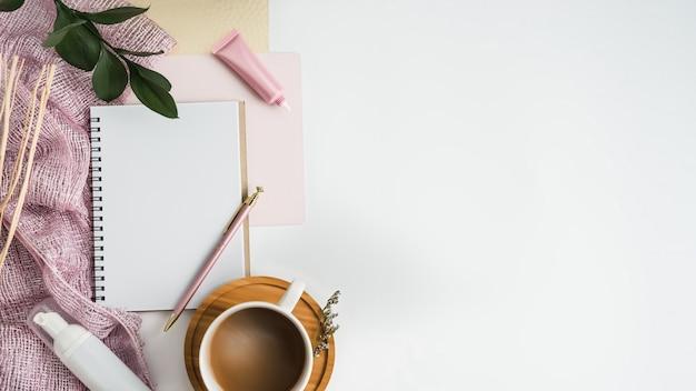 スタイリッシュな空白のノートとコーヒーカップと白いオフィスの机のテーブル。