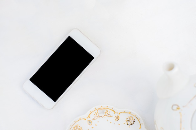 Стильный белый рабочий стол с современным телефоном.