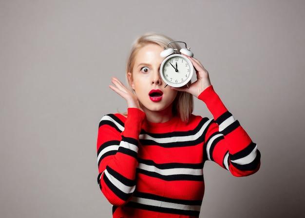 灰色の壁に目覚まし時計と赤いセーターのスタイルの女性