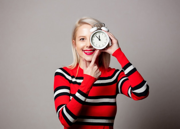 Styled woman in red sweater with alarm clock on grey wall