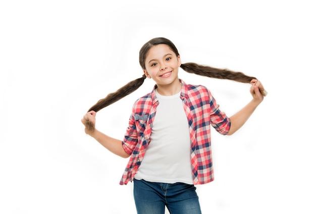 그녀가 좋아하는 방식으로 머리를 스타일링합니다. 아름다운 외모를 가진 작은 머리 모델. 세련된 포니테일 헤어스타일을 한 어린 소녀입니다. 갈색 머리를 가진 작은 아이. 긴 헤어스타일을 가진 예쁜 소녀입니다. 아이들을 위한 미용실.