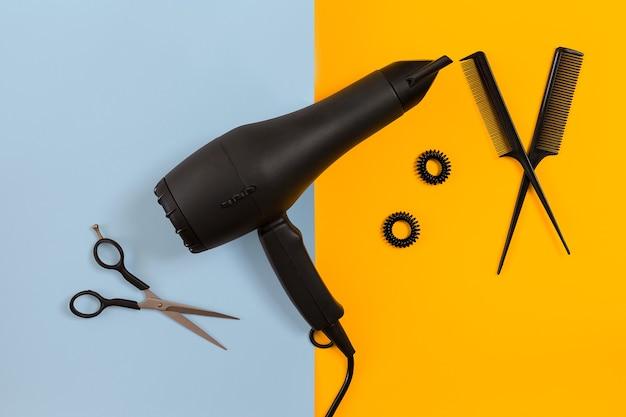 Укладка волос ножницами, феном и инструментами в парикмахерской на синем и желтом бумажном фоне. вид сверху. скопируйте пространство. плоская планировка. натюрморт. макет