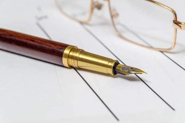 Стильная ручка и очки лежит на простыне