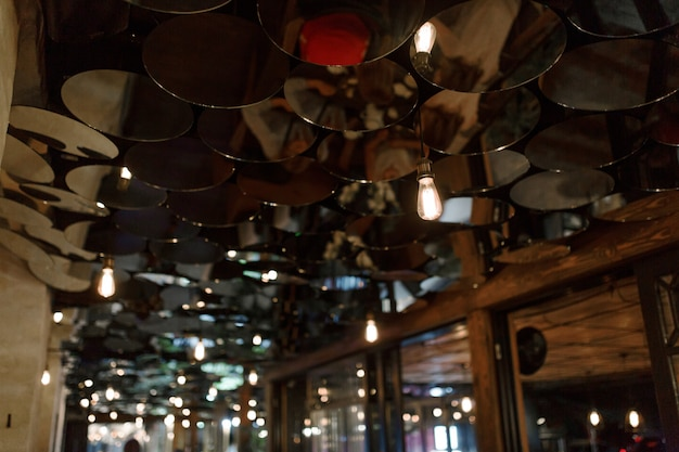 Stylish abstract bar interior. the ceiling is decorated with small round mirrors.