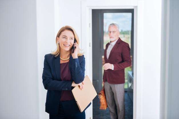 スタイリッシュなアクセサリー。在宅勤務中に電話を受けるスタイリッシュなアクセサリーを身に着けている魅力的な実業家を輝かせる