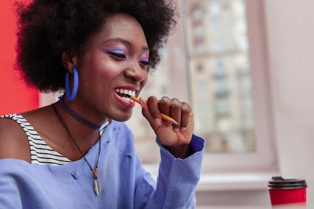 세련된 액세서리. 연필 들고 세련 된 액세서리를 착용하는 크리 에이 티브 아프리카 계 미국인 디자이너