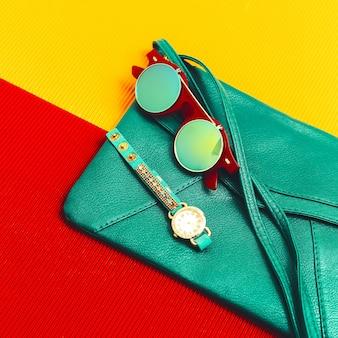 세련된 액세서리. 녹색 가죽 클러치, 시계 및 선글라스. 패션 레이디가 되십시오