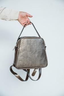 白い背景で隔離のスタイリッシュなアクセサリー。女性の手でブロンズ色のバッグ