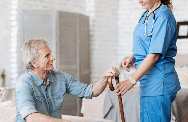 スタイリッシュなアクセサリー。立派な優しい医療従事者がリクエストに応え、アパートを少し散歩する老人を助けます