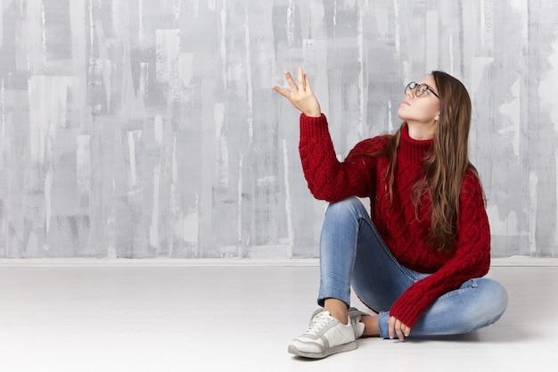 暖かいニットのプルオーバー、デニムパンツ、スニーカー、眼鏡を身に着けたスタイリッシュで愛らしい長髪の女の子が、床に快適に座って身振りで示す