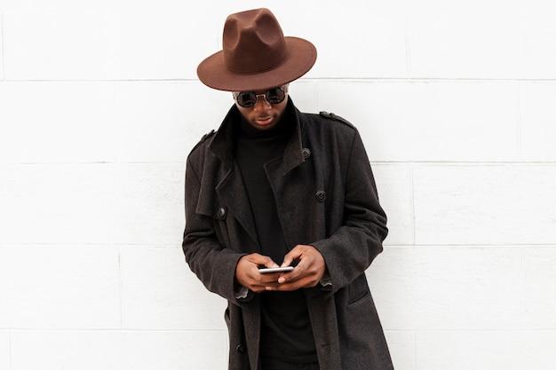 Maschio adulto alla moda che propone con il cappello e gli occhiali da sole