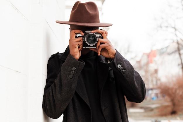 Стильный взрослый мужчина фотографируя с камерой