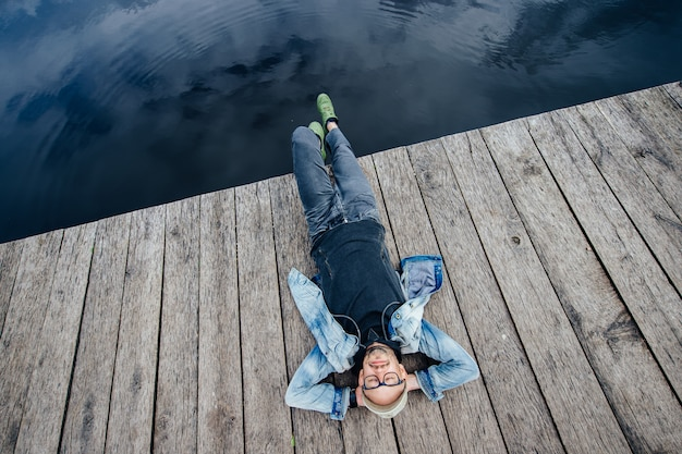 Stylish adult man lying on old wooden pier beyond lake. dreaming happy bearded hipster in glasses portrait from above.