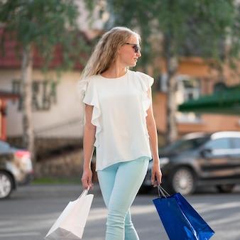 買い物袋を運ぶスタイリッシュな大人の女性