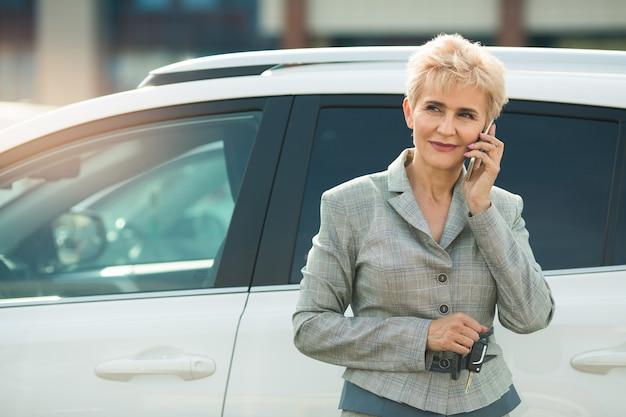 Стильная взрослая женщина в костюме с мобильным телефоном возле машины