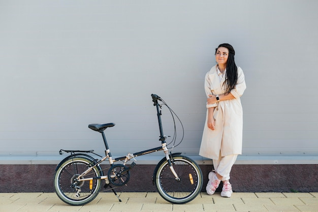 Stylish adult woman posing with eco friendly bike