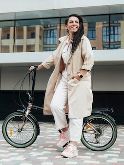 環境にやさしい自転車でポーズをとるスタイリッシュな大人の女性