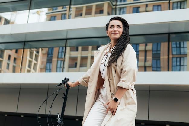 Стильная взрослая женщина позирует с экологически чистым велосипедом