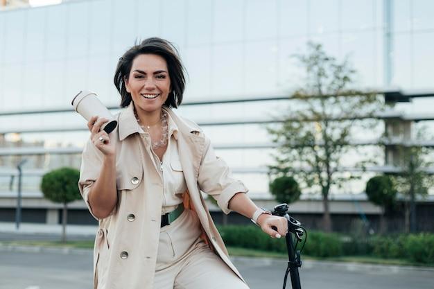 Stylish adult woman posing with eco friendly bike