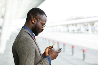 Stylish African American black businessman types information from his credit card