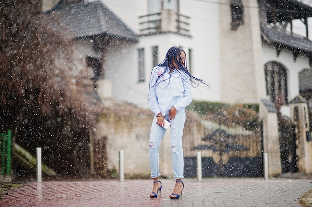 Stylish african american girl with dreads holding mobile phone at hand, outdoor snowy weather.