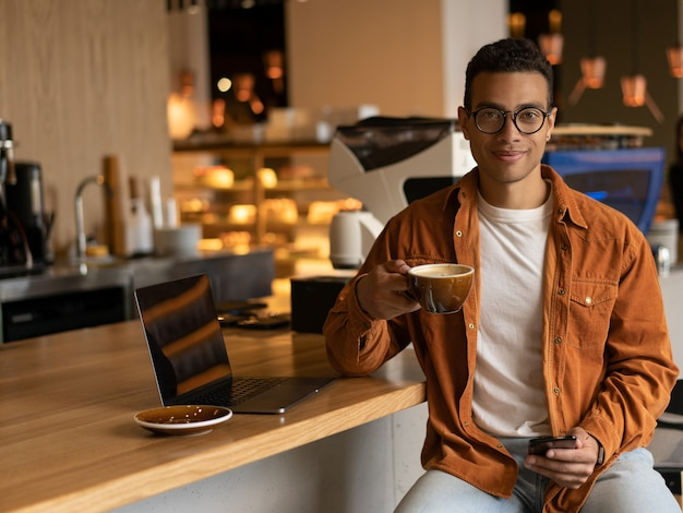Stylish african american man freelancer holding cup of coffee, using mobile phone sitting in modern cafe