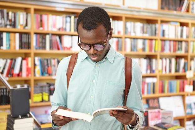 Стильный афро-американский мужчина в библиотеке