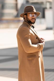 Стильный афро-американский мужчина позирует на открытом воздухе
