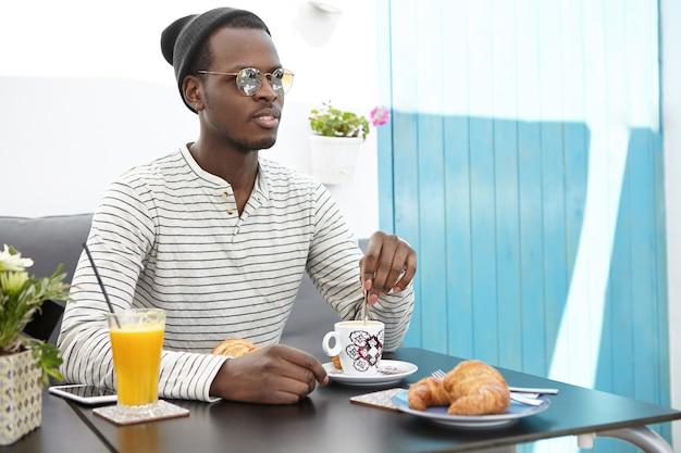 カフェに座っているスタイリッシュなアフリカ系アメリカ人の男