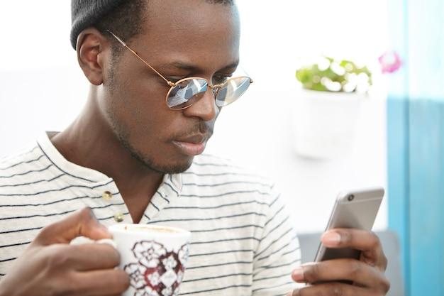 Стильный афро-американский мужчина сидит в кафе
