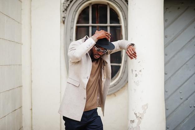 スタイリッシュなアフリカ系アメリカ人の男性は、ヴィンテージの窓にサングラスのポーズでベージュのジャケットと黒い帽子を着用します。