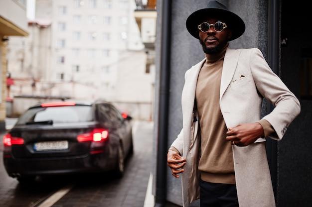 スタイリッシュなアフリカ系アメリカ人の男性は、車の近くでポーズをとるベージュのジャケットとサングラスの黒い帽子を着用します。