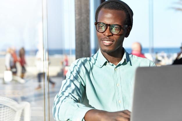 ノートパソコンを持つスタイリッシュなアフリカ系アメリカ人の男