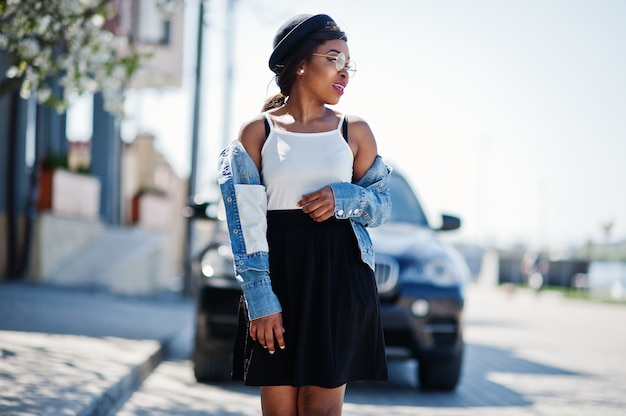 Stylish african american model in glasses hat, jeans jacket and black skirt posed outdoor against black business suv car.