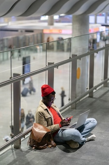 Stylish african american traveler millennial man resting and sitting on the floor in airport, using cellphone.